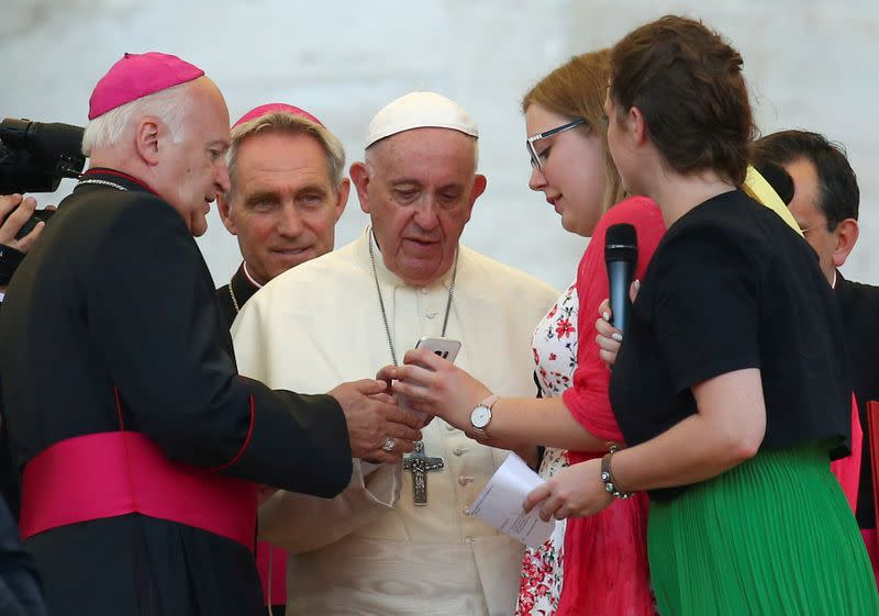 FILE PHOTO: Pope Francis sends a message on a mobile phone at the end of a special audience with altar servers in Saint Peter's square at the Vatican