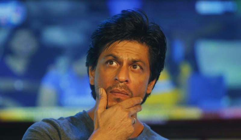 FILE - In this Aug. 14, 2012 file photo,  Bollywood star Shah Rukh Khan gestures as he speaks to media during an event in Mumbai, India. Khan jokes that he will wear a mask and sneak into a Mumbai stadium to watch his cricket team play in the Indian Premier League. Khan was banned from the stadium for five years in 2012 after he was involved in a scuffle with security. (AP Photo/Rafiq Maqbool, File)