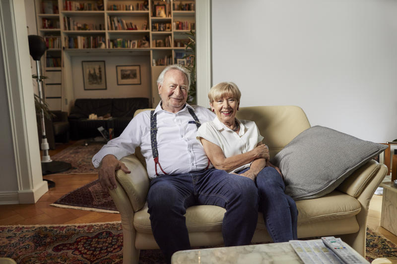 Portrait of smiling senior couple sitting on couch at home