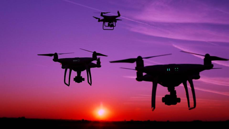drones ascending into the night in front of a sunset