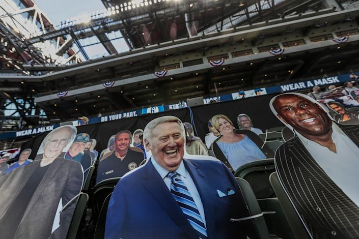 Cardboard cutouts of Vin Scully and Magic Johnson behind the Dodgers' dugout.
