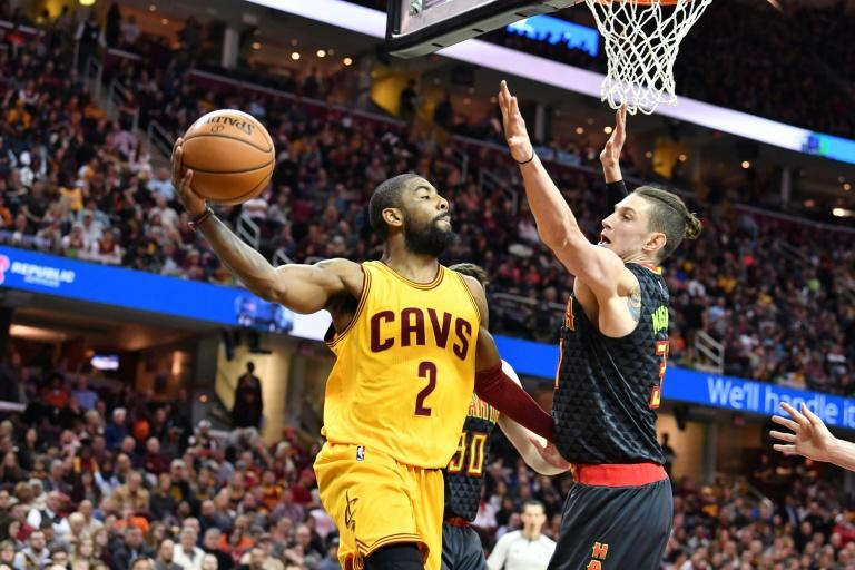 Kyrie Irving of the Cleveland Cavaliers passes around Ryan Kelly of the Atlanta Hawks during the first half at Quicken Loans Arena in Cleveland, Ohio