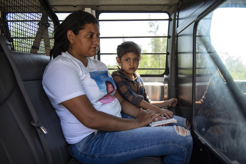 Illegal immigrants are loaded into a van after being detained