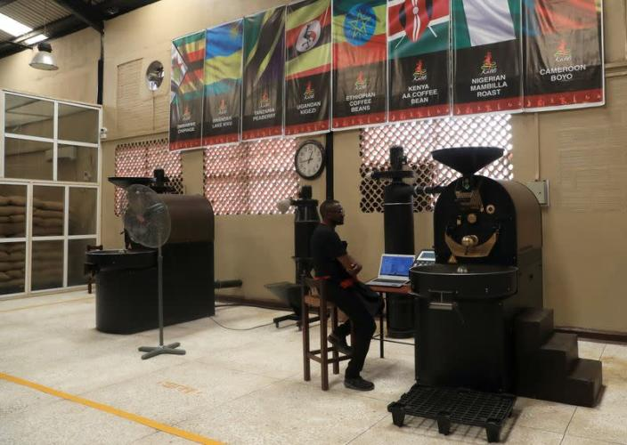 An employee sits beside coffee beans roaster at Kaldi Africa coffee roastery in Lagos