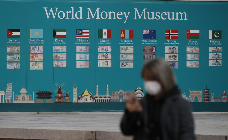 """A woman wearing a face mask walks near a board displaying the foreign currencies in downtown Seoul, South Korea, Saturday, Feb. 29, 2020. The coronavirus outbreak's impact on the world economy grew more alarming on Saturday, even as President Donald Trump denounced criticisms of his response to the threat as a """"hoax"""" cooked up by his political enemies. (AP Photo/Lee Jin-man)"""