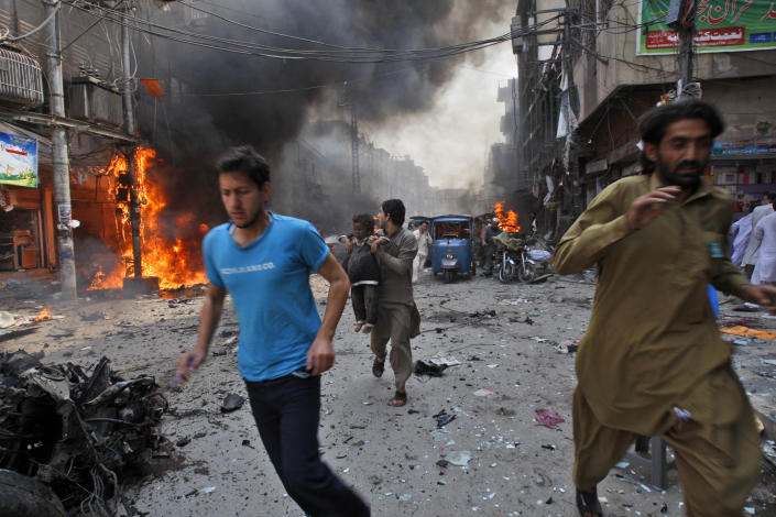 Pakistani run away from the site of a blast shortly after a car explosion in Peshawar, Pakistan, Sunday, Sept. 29, 2013. A car bomb exploded on a crowded street in northwestern Pakistan Sunday, killing scores of people in the third blast to hit the troubled city of Peshawar in a week, officials said. (AP Photo/Mohammad Sajjad)