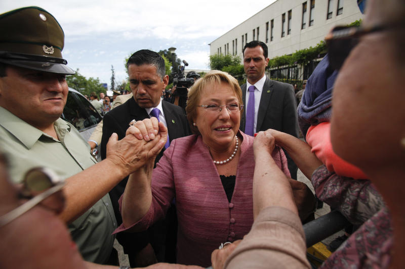 Chile's former President Michelle Bachelet greets supporters as she leaves a polling station after voting in general elections in Santiago, Chile, Sunday, Nov. 17, 2013. Bachelet is the front runner and conservative Evelyn Matthei is a distant second in Sunday's election for Chile's presidency. Other candidates could push the vote into a Dec. 15 runoff. (AP Photo/Luis Hidalgo)