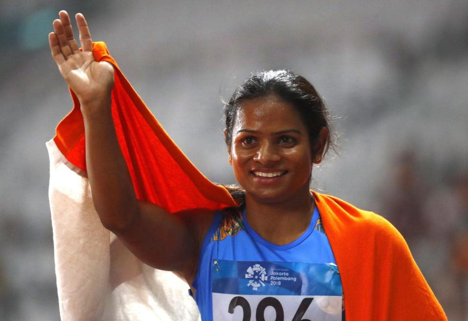 Athlete, with an Indian flag draped around her shoulders, raises one arm to wave at the crowd.