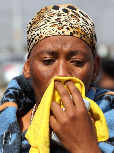 An unidentified family member reacts during a memorial service at the Lonmin Platinum Mine near Rustenburg, South Africa, Thursday, Aug. 23, 2012. Police shot and killed 34 striking miners and wounded 78 last week. Demands for higher wages spread to at least two other mines, raising fears of further protests at more South African mines that provide most of the world's platinum. (AP Photo/Themba Hadebe)