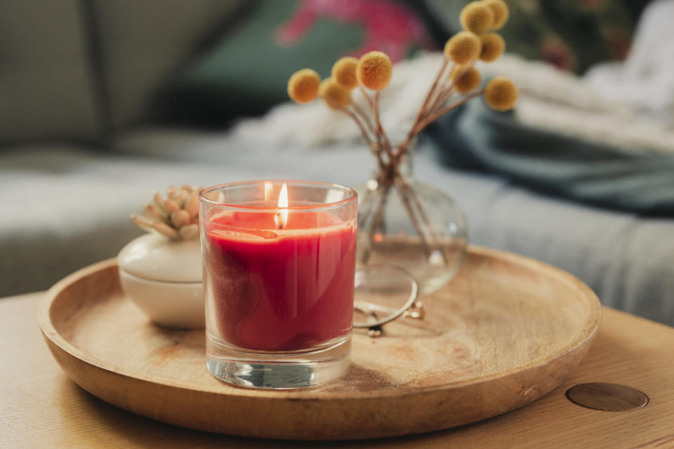 Scented candle burning on sofa table Photo taken in natural light