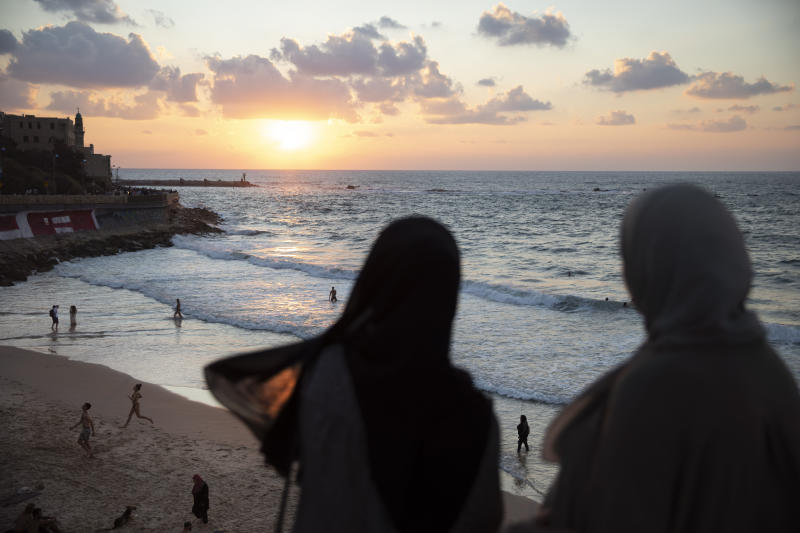 In this Monday, Sept. 23, 2019 photo, Two Israeli Arab women overlook the Mediterranean sea, in the mixed Arab and Jewish city of Jaffa, near Tel Aviv, Israel. Electoral gains made by Arab parties in Israel, and their decision to endorse one of the two deadlocked candidates for prime minister, could give them new influence in parliament. But they also face a dilemma dating back to Israel's founding: How to participate in a system that they say relegates them to second-class citizens and oppresses their Palestinian brethren in Gaza and the occupied West Bank. (AP Photo/Oded Balilty)