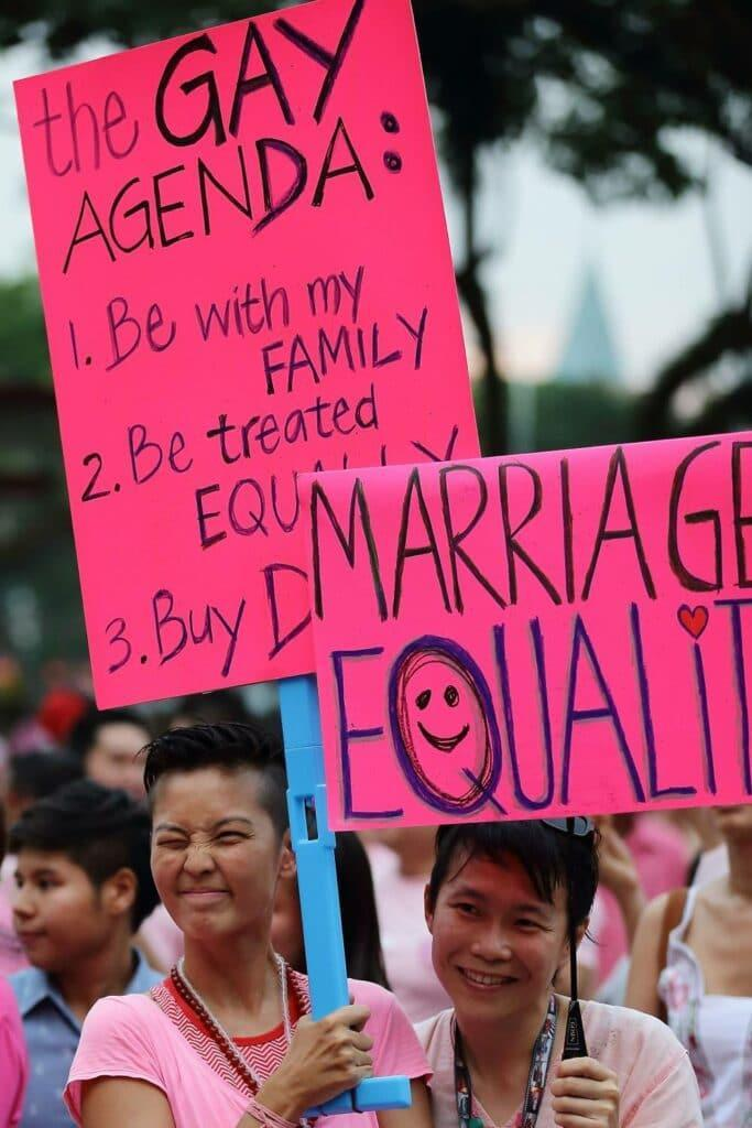 Participants hold up signs supporting Singapore's LGBT+ community