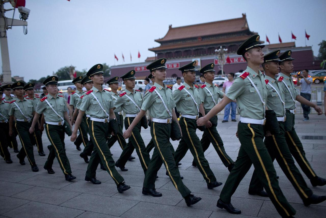 Paramilitary policemen march on Tiananmen Square after a flag-lowering ceremony on Tiananmen Square in Beijing, China, Wednesday, June 4, 2014. Heavy security blanketed central Beijing on the 25th anniversary of the bloody suppression of the Tiananmen Square pro-democracy protests on Wednesday, pre-empting any attempts to publicly commemorate one of the darkest chapters in recent Chinese history. (AP Photo/Alexander F. Yuan)