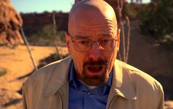 Walter White has teary eyes and a mouth open in shock; he is at an outdoor location with rocks and desert