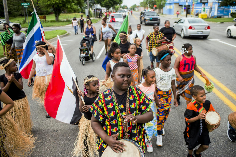 Zebiyan Fields, 11, at center, drums alongside more than 20 kids at the front of the Juneteenth parade in Flint, Michigan on June 19, 2018. (Jake May / AP)