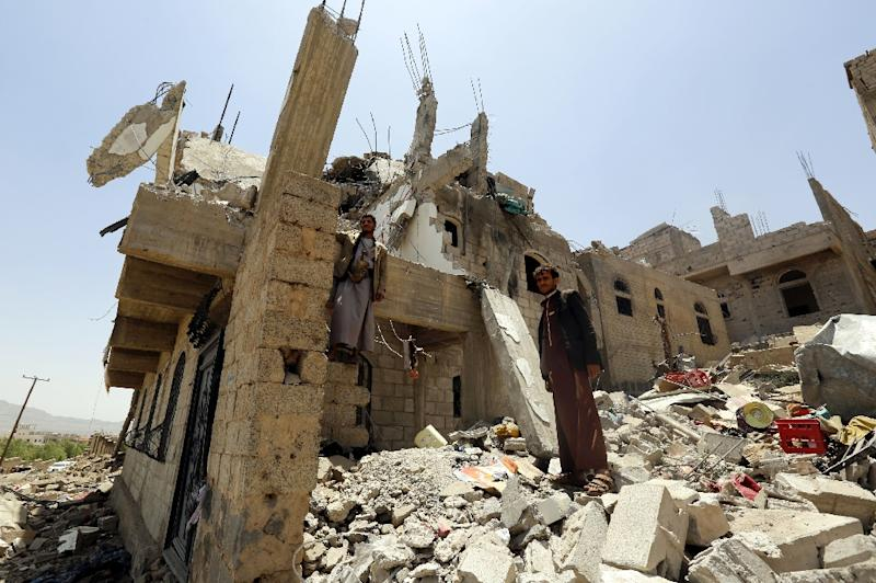 Yemenis stand in the rubble of destroyed buildings in the Al-Nahda neighbourhood of Sanaa, following intensified Saudi-led coalition air strikes on September 6, 2015 (AFP Photo/Mohammed Huwais)