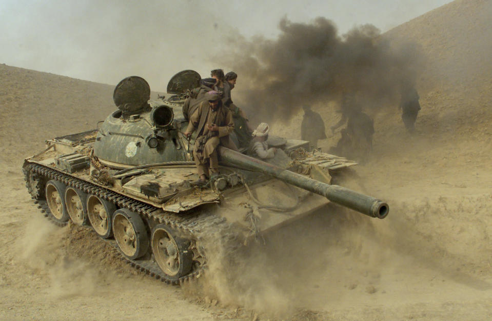 Defecting Taliban fighters maneuver a tank through the front line near the village of Amirabad, between Kunduz and Taloqan, Saturday, Nov. 24, 2001. (AP Photo/Jerome Delay)