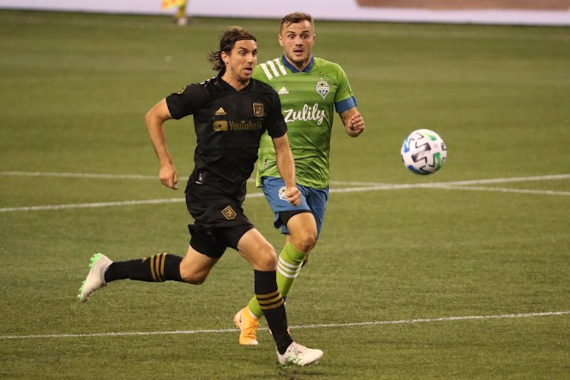 SEATTLE, WASHINGTON - AUGUST 30: Dejan Jakovic #5 of Los Angeles FC and Jordan Morris #13 of Seattle Sounders chase the ball in the second half at CenturyLink Field on August 30, 2020 in Seattle, Washington. (Photo by Abbie Parr/Getty Images)