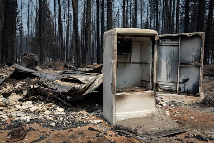 A burned and empty refrigerator sits amid fire-strewn rubble