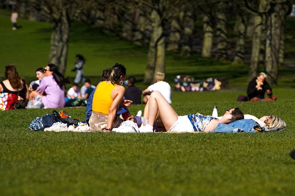 Members of the public enjoy the hot weather in Hyde Park, Leeds. (PA)