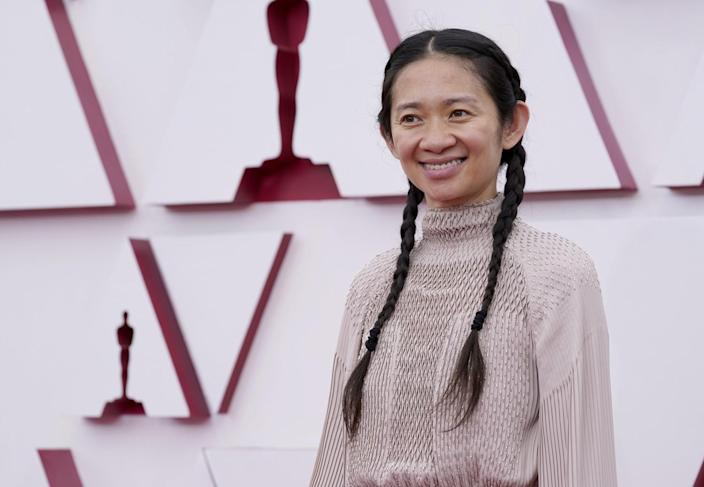 Chloé Zhao in braids wearing a light, high-neck dress.