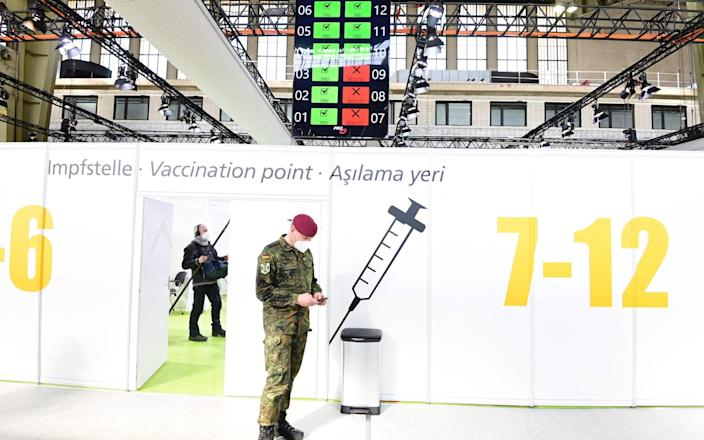 A soldier of the German Armed Forces Bundeswehr stands inside a new vaccination centre at the former Tempelhof airport in Berlin before its opening on March 8, 2021. (Photo by Tobias Schwarz / various sources / AFP) (Photo by TOBIAS SCHWARZ/POOL/AFP via Getty Images) - TOBIAS SCHWARZ/AFP