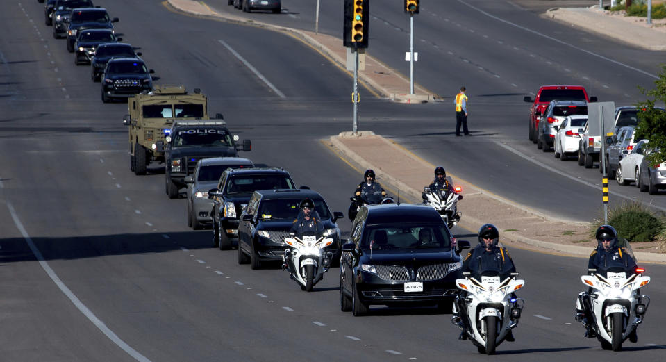 After departing from Bring's Broadway Chapel, a hearse and law enforcement procession for Drug Enforcement Administration Supervisory Special Agent Michael G. Garbo travels down E. Broadway Blvd. in Tucson, Ariz. on Friday, Oct. 8, 2021. Garbo, a federal agent shot and killed while questioning a passenger on an Amtrak train in Arizona, was remembered Friday as a venerated leader and mentor with an unparalleled work ethic. (Rebecca Sasnett/Arizona Daily Star via AP)