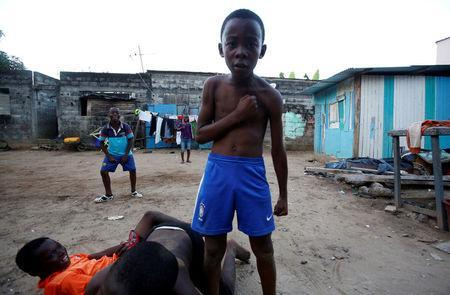 Jean-Christ, 11, celebrates his goal during a football game in an area of Riviera-Palmeraie in Abidjan, Ivory Coast May 28, 2018. REUTERS/Thierry Gouegnon