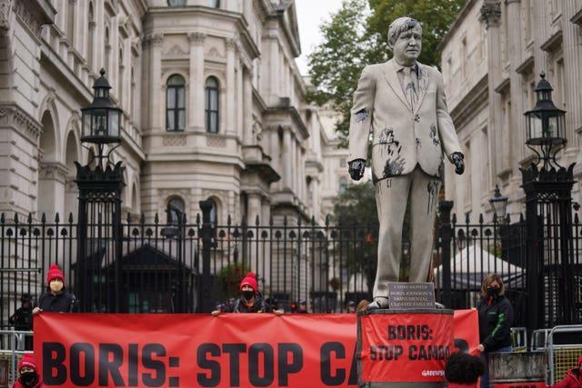 Greenpeace demonstrators outside Downing Street with a statue of Prime Minister Boris Johnson splattered with oil (Victoria Jones/PA)