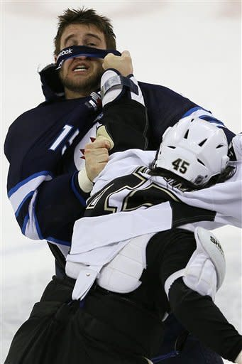 Winnipeg Jets forward Tanner Glass (15) and Pittsburgh Penguins' forward Arron Asham (45) fight during first-period NHL hockey game action in Winnipeg, Manitoba, Friday, Dec. 23, 2011. (AP Photo/The Canadian Press, John Woods)