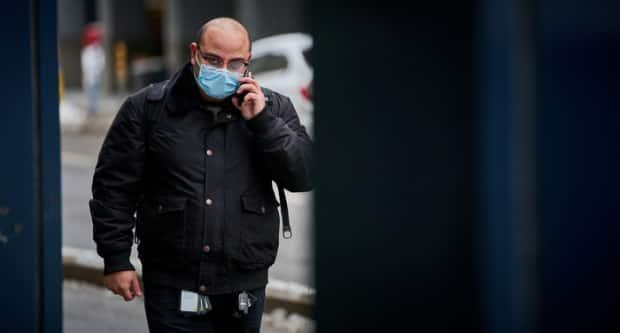 A man wearing a mask speaks on the phone in downtown Ottawa in February 2021.