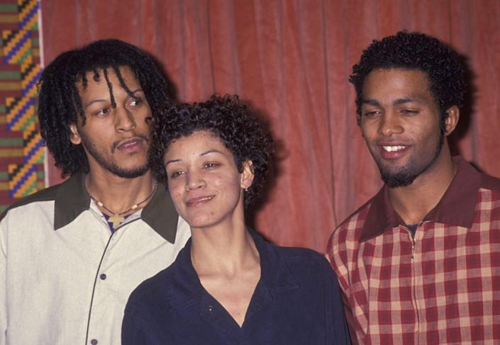 Three hip-hop artists stand together posing for a photo.