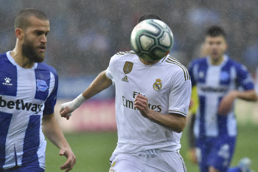 Real Madrid's Karim Benzema, right, goes for the ball beside Alaves' Victor Laguardia during the Spanish La Liga soccer match between Real Madrid and Alaves at Mendizorroza stadium, in Vitoria, northern Spain, Saturday, Nov. 30, 2019. (AP Photo/Alvaro Barrientos)