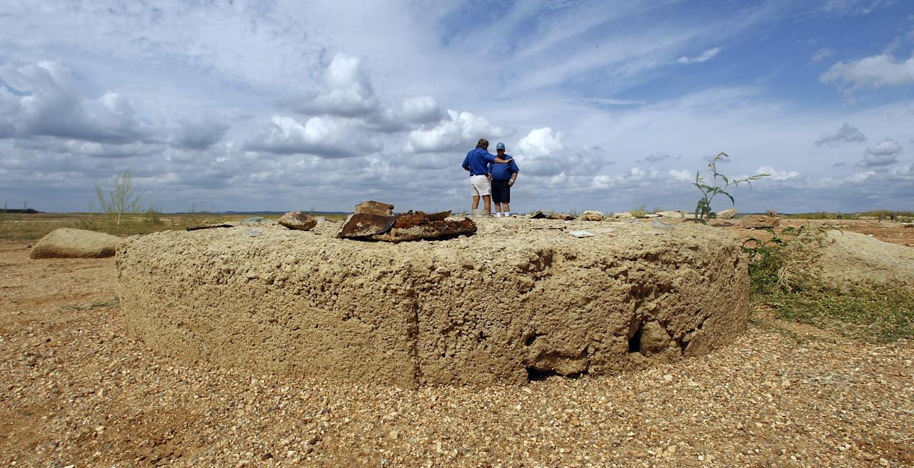 In this Oct. 5, 2011 photo, a mold for wagon wheels has joined other remnants of old Bluffton, Texas, resurfacing on the now dry, sandy lake near Bluffton, as the Texas drought shrinks the state's largest inland lake. (AP Photo/Eric Gay)