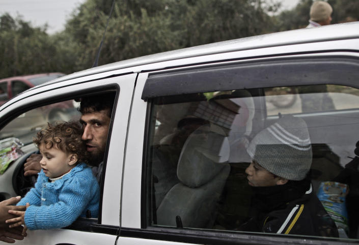 In this Thursday, Dec. 13, 2012, photo, A Syrian rebel and his children sit in a car, in Maaret Misreen, near Idlib, Syria. The town is broke, relying on a slowing trickle of local donations. The rebels, a motley crew of laborers, mechanics and shopowners, have little experience in government. President Bashar Assad's troops still control the city of Idlib a few miles away, making area roads unsafe and keeping Maaret Misreen cut off from most of Syria.(AP Photo/Muhammed Muheisen)