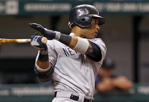 New York Yankees' Robinson Cano hits a two-run single during the eighth inning of a baseball game against the Tampa Bay Rays, Wednesday, July 4, 2012, in St. Petersburg, Fla. The Yankees won 4-3. (AP Photo/Mike Carlson)