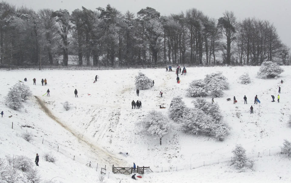 People exercise in the fresh snow at Wye National Nature Reserve near Ashford, southern England, Sunday Feb. 7, 2021. Heavy snow is predicted for the coming days and set to bring disruption to south-east England as bitterly cold winds grip much of the nation. (Andrew Matthews/PA via AP)