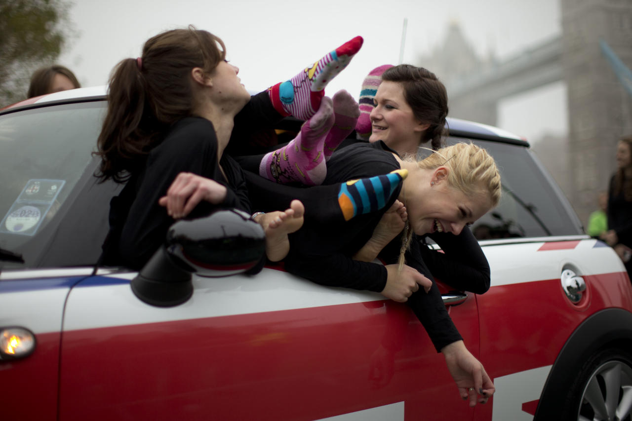 Participants laugh as they get themselves positioned to pose for mock-up photographs for the media after getting back in the car following a successful Guinness World Record attempt to fit 28 ladies into a Mini car backdropped by Tower Bridge in London, Thursday, Nov. 15, 2012.  The attempt which broke the previous record of 27 people, was made to coincide with Guinness World Records Day, an annual event which organizers estimate will see in the region of 420,000 people attempting records around the globe.  (AP Photo/Matt Dunham)