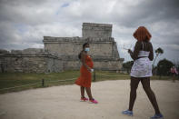 Tourists, required to wear protective face masks amid the new coronavirus pandemic, visit the Mayan ruins of Tulum in Quintana Roo state, Mexico, Tuesday, Jan. 5, 2021. Tourism accounts for 87% of Quintana Roo's gross domestic product, said state Tourism Secretary Marisol Vanegas. The state lost some 90,000 tourism jobs in the formal economy that depend on tourism due to the new coronavirus pandemic. (AP Photo/Emilio Espejel)