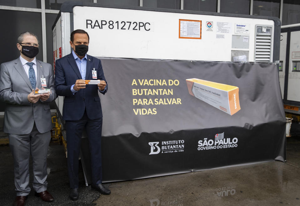 Sao Paulo state Health Secretary Dr. Jean Gorinchteyn, left, and Sao Paulo Governor Joao Doria pose for photos next to a container carrying the experimental COVID-19 vaccine CoronaVac after several were unloaded from a cargo plane that arrived from China at Guarulhos International Airport in Guarulhos, near Sao Paulo, Brazil, Thursday, Nov. 19, 2020. The experimental vaccine is being tested in a partnership with the Butantan Institute and Chinese pharmaceutical company Sinovac. (AP Photo/Andre Penner)