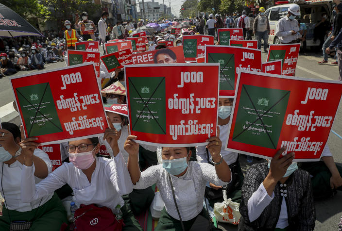 """Anti-coup protesters stage a sit-in protest in Mandalay, Myanmar, Wednesday, Feb. 24, 2021. Protesters against the military's seizure of power in Myanmar were back on the streets of cities and towns on Wednesday, days after a general strike shuttered shops and brought huge numbers out to demonstrate. Placards reads as """"Abolish 2008 Military Slave Law."""" (AP Photo)"""