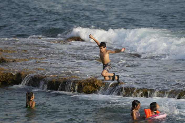 A boy jumps in the water on Batroun beach in Batroun village, north of Beirut, Lebanon, Friday, July 2, 2021. With their dollars trapped in the bank, a lack of functioning credit cards and travel restrictions imposed because of the pandemic, many Lebanese who traditionally vacationed over the summer at regional hotspots are also now turning toward domestic tourism. (AP Photo/Hassan Ammar)