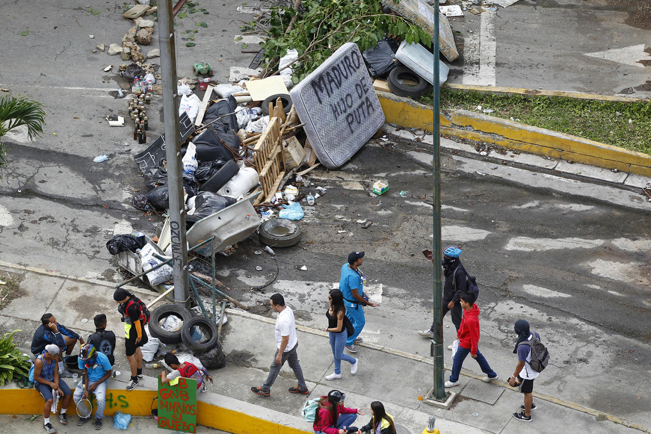 "<p>People walk past a street barricade that includes a mattress with the words ""Maduro son of a bitch"" after clashes broke out while the Constituent Assembly election was being carried out in Caracas, Venezuela, July 30, 2017. (Christian Veron/Reuters) </p>"