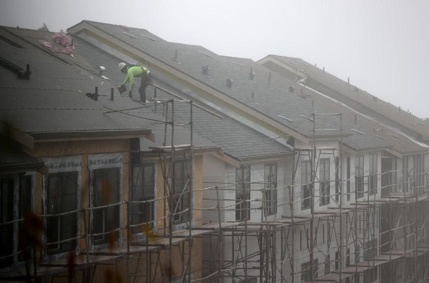 SOUTH SAN FRANCISCO, CALIFORNIA - SEPTEMBER 24: A worker stands on the roof of a new home under construction on September 24, 2020 in South San Francisco, California. Sales of new single-family homes rose 4.8 percent in August and surpassed an annual rate of 1 million for the first time in 14 years. (Photo by Justin Sullivan/Getty Images)