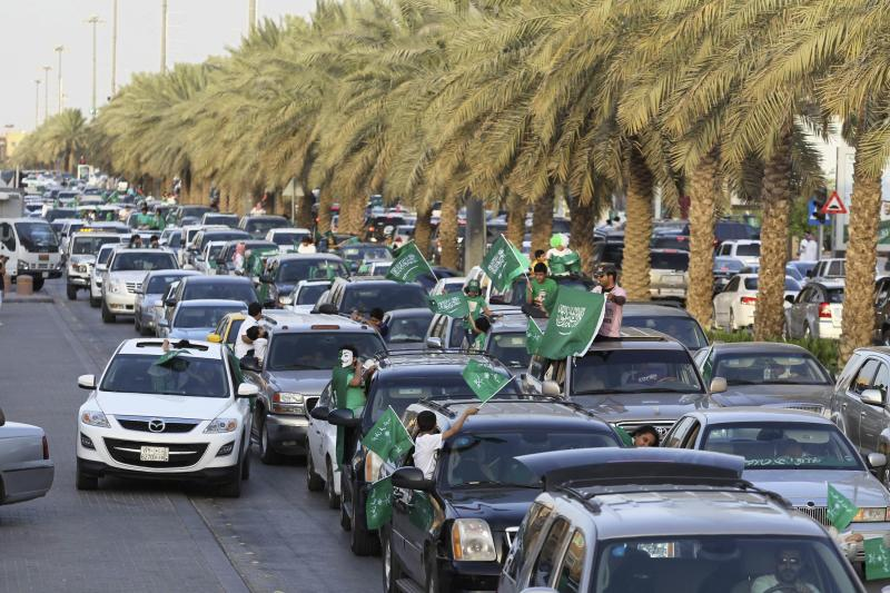 Boys wave Saudi Arabia's national flag as they ride a car, as the oil-rich Gulf Arab country celebrates its National Day, in Riyadh September 23, 2013. REUTERS/Faisal Al Nasser (SAUDI ARABIA - Tags: POLITICS ANNIVERSARY)