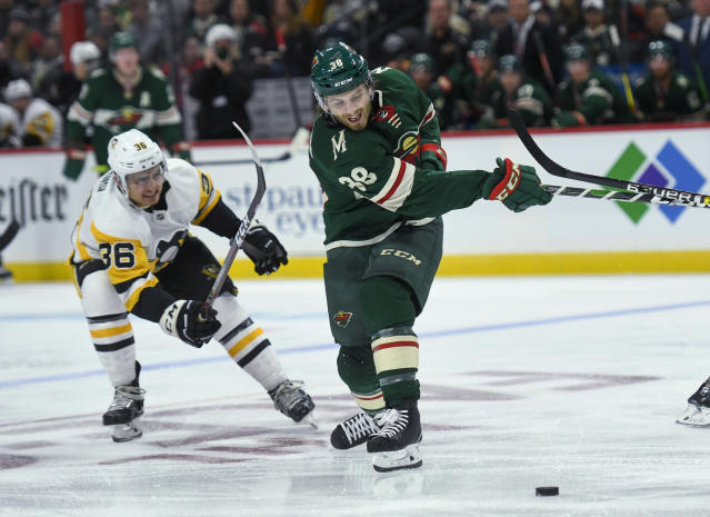 Minnesota Wild winger Ryan Hartman, right, shoots as Pittsburgh Penguins winger Joseph Blandisitries to stop the shot during the second period of an NHL hockey game Saturday, Oct. 12, 2019, in St. Paul, Minn. (AP Photo/Craig Lassig)