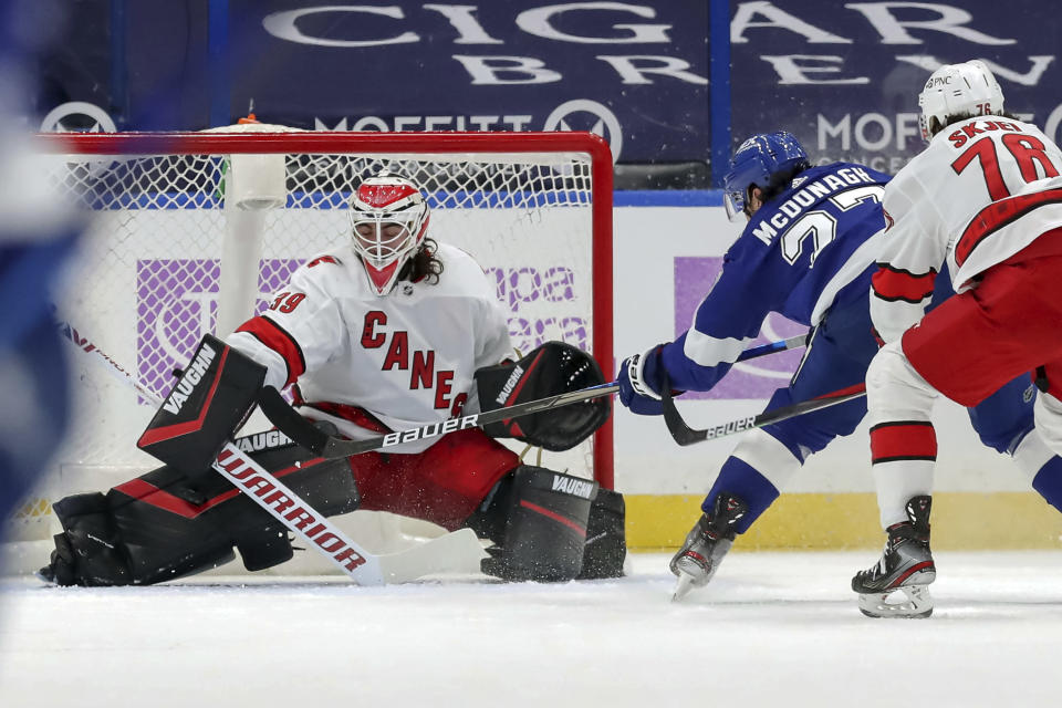 Carolina Hurricanes goaltender Alex Nedeljkovic makes a pad save on a shot from Tampa Bay Lightning's Ryan McDonagh as Steven Lorentz (78) defends during the first period of an NHL hockey game Tuesday, April 20, 2021, in Tampa, Fla. (AP Photo/Mike Carlson)