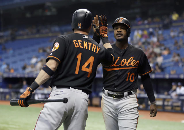 Baltimore Orioles' Adam Jones (10) high-fives Craig Gentry (14) after Jones scored on a double by Danny Valencia off Tampa Bay Rays starting pitcher Sergio Romo during the first inning of a baseball game Friday, May 25, 2018, in St. Petersburg, Fla. (AP Photo/Chris O'Meara)