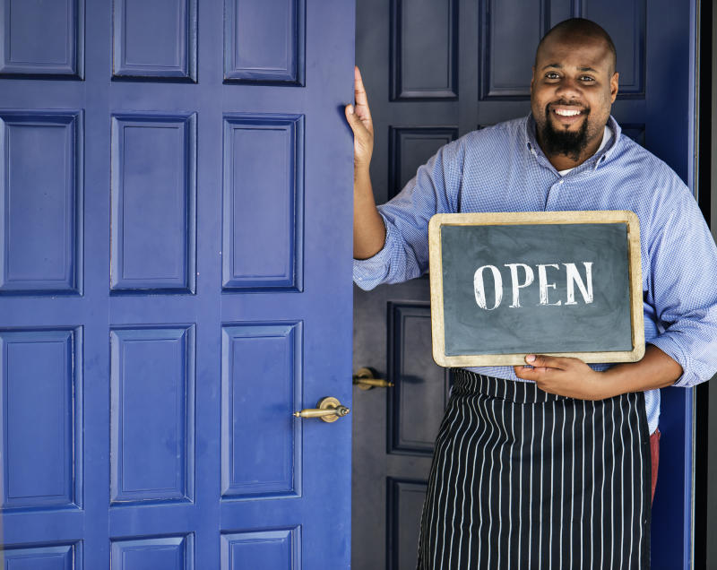 """A happy cafe owner stands in an apron at the entrance to his business and holds a chalkboard sign which says """"Open."""""""