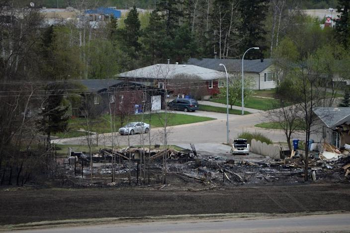 A burned-out house and others still intact are shown in the Abasands neighbourhood during a media tour of the fire-damaged city of Fort McMurray, Alberta, Canada on May 9, 2016 (AFP Photo/Jonathan Hayward)